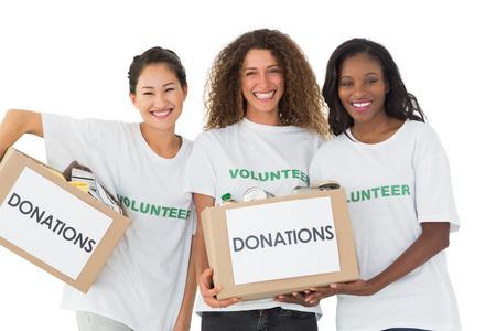 altruismo: Feliz equipo de voluntarios que sonr�en a la c�mara sosteniendo donaciones cajas en el fondo blanco