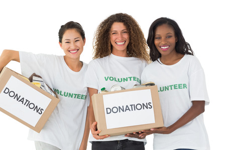 volunteerism: Happy team of volunteers smiling at camera holding donations boxes on white background Stock Photo