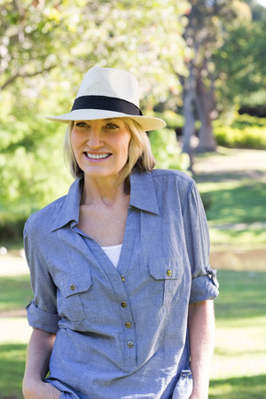 sunhat: Happy woman wearing sunhat looking away in park