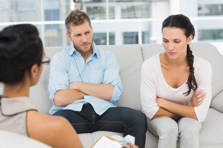 marriage counseling: Unhappy couple with arms crossed at therapy session in therapists office
