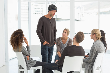 introducing: Rehab group listening to man standing up introducing himself at therapy session Stock Photo