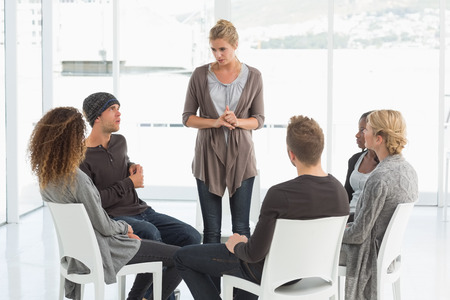 Rehab group listening to woman standing up introducing herself at therapy session Stock Photo