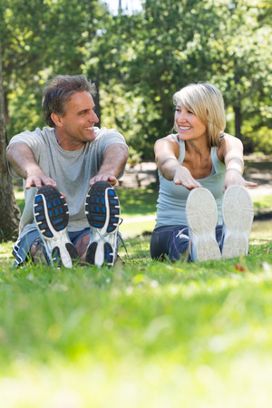 Happy couple looking at each other while stretching in the park photo