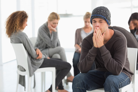 Upset man at rehab group with hands to face at therapy session Stock Photo