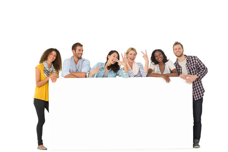Happy group of young friends leaning on large poster on white background photo