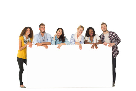 Smiling group of young friends leaning on large poster  on white background photo