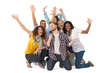 Smiling group of young friends having fun doing karaoke on white background photo