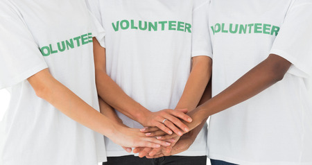 selfless: Team of volunteers putting hands together on white background