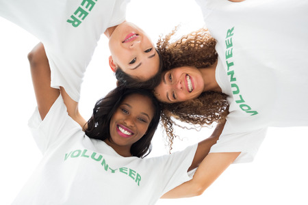 altruismo: El equipo de voluntarios felices abrazando y mirando a la c�mara sobre fondo blanco Foto de archivo