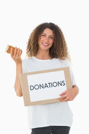 altruismo: Voluntario feliz que sostiene una caja de donaciones y tarro de mermelada en el fondo blanco