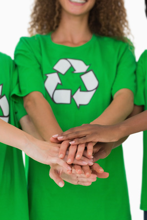 activists: Team of environmental activists putting hands together on white background