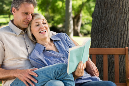 Happy loving couple reading book on park bench photo