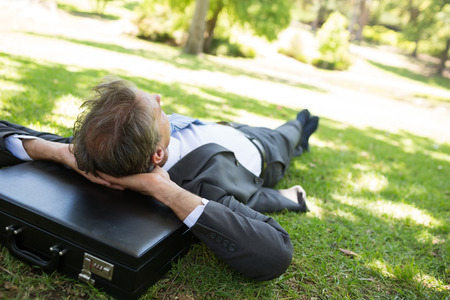 Businessman resting head on briefcase while lying in park photo