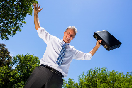 Low angle portrait of happy businessman with arms outstretched carrying briefcase against blue sky photo
