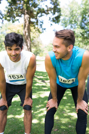 Smiling Male Marathon Runners Talking In Park Stock Photo
