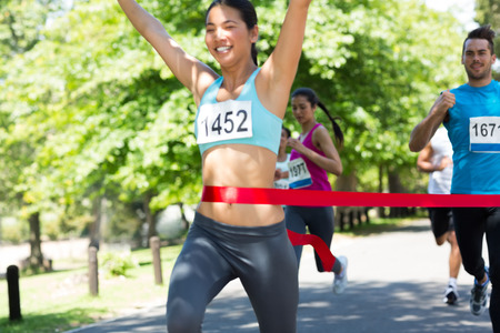 Young marathon runner with arms raised crossing finish line photo