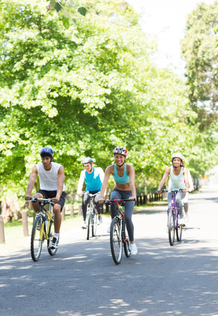Cyclists riding bicycles on country road photo