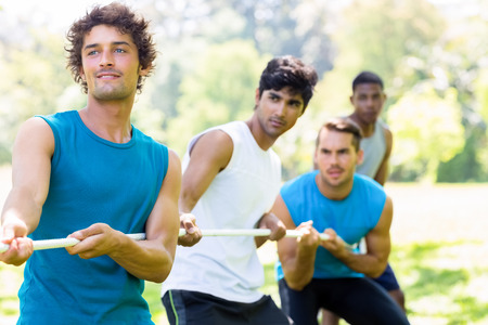 Group of male friends playing tug of war in park photo