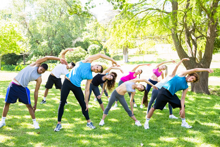 Full length of people doing stretching exercise in the park photo