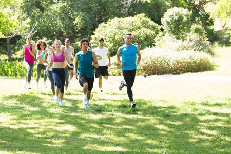 公園の草が茂った土地を実行している運動選手のグループ 写真素材