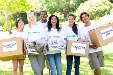 text box: Group portrait of cheerful volunteers carrying donation boxes in park