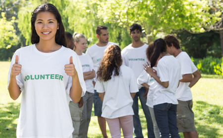 environmental conversation: Portrait of confident volunteer gesturing thumbs up at park with friends in backgorund