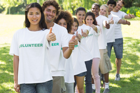 altruism: Retrato de voluntarios confiados que gesticulan los pulgares para arriba mientras que de pie en una línea en el parque Foto de archivo