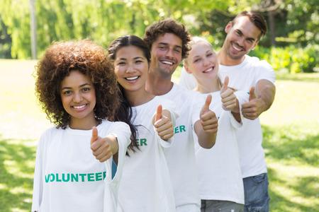 altruismo: Retrato de j�venes voluntarios confiados gesticula los pulgares para arriba en el parque