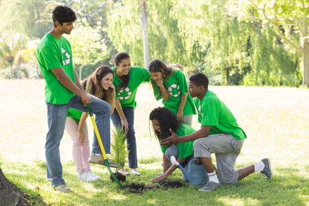 Group of young environmentalists planting in park photo