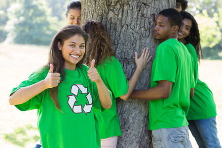 Portrait of confident female environmentalist showing thumbs up with friends hugging tree in background