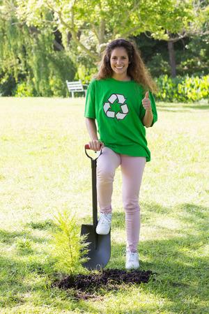 altruism: Retrato del ambientalista femenino confidente que gesticula los pulgares arriba en el parque