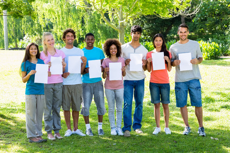blank papers: Portrait of confident university students holding blank papers on campus