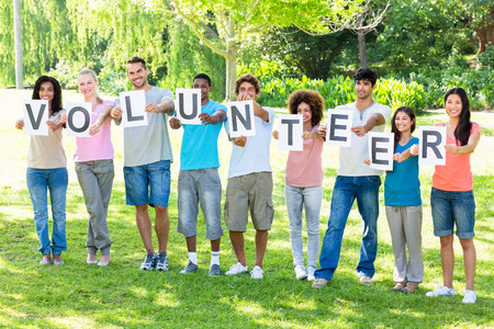Full length of friends holding placards spelling volunteer on campus photo