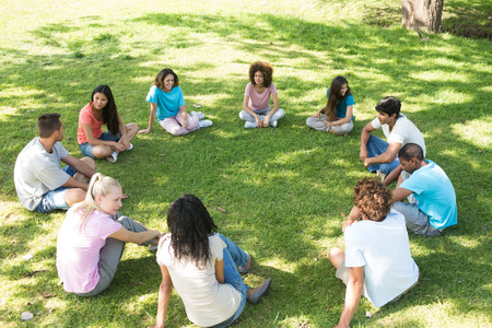 Group of multiethnic friends sitting in a circle at park photo