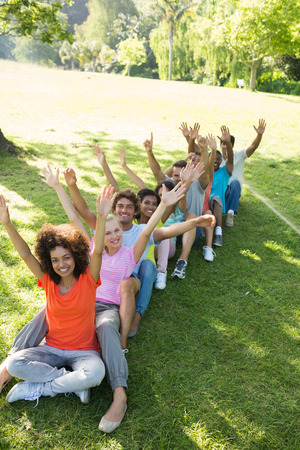 High angle view of happy friends raising hands while sitting on grass in park photo
