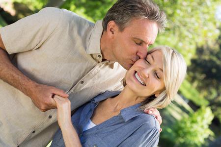 hombre romantico: Hombre rom�ntico besa a la mujer mientras mantiene las manos en el parque