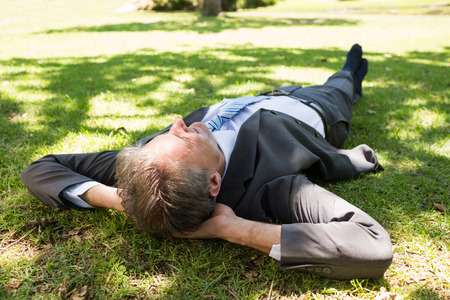 Full length of businessman lying on grass in park photo