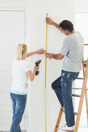 Rear view of a woman holding drill while man measuring the wall at new home photo