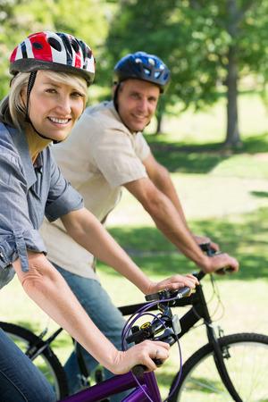 cicla: Retrato de mujer hermosa con el hombre andar en bicicleta en un parque Foto de archivo