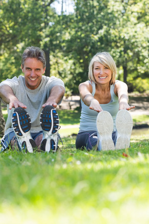 Full length portrait of happy couple stretching in the park photo
