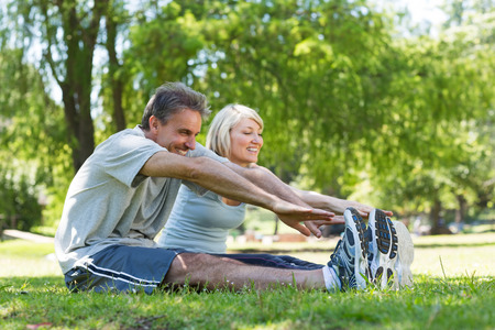 active lifestyle: Happy couple stretching while sitting on grass in the park