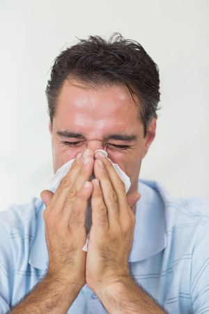 Closeup of a man suffering from cold with eyes closed photo
