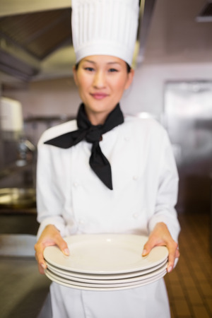 Portrait of a smiling female cook holding empty plates in the kitchen photo