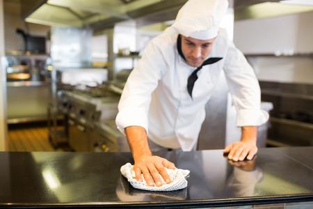 keuken restaurant: Mannelijke kok afvegen van de aanrechtblad in de keuken Stockfoto