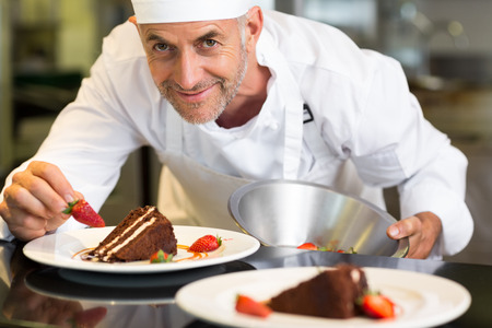 Closeup portrait of a smiling male pastry chef decorating dessert in the kitchen photo