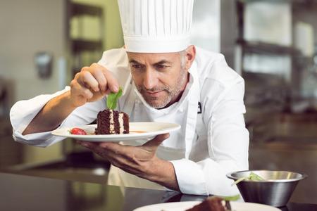 Close-up van een geconcentreerde mannelijke banketbakker decoreren dessert in de keuken Stockfoto