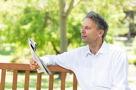 well read: Relaxed businessman reading newspaper in the park