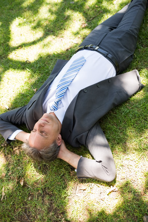 High angle view of businessman relaxing on grass in park photo