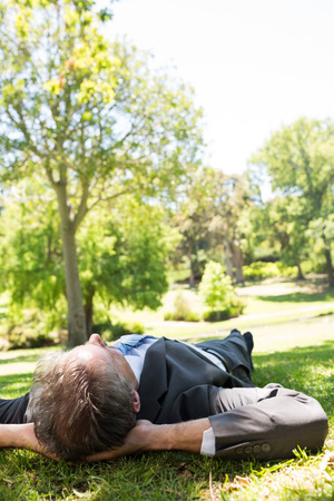 Relaxed businessman lying on grass in park photo