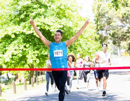 興奮して男性ランナー、マラソンの finshline を横断
